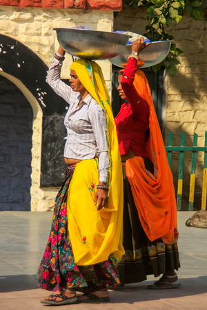 Local women carrying metal buckets on their heads in Agra, Uttar Pradesh, India. Agra is one of the most populous cities in Uttar Pradesh