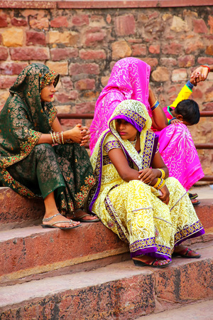 Local women sitting on the steps outside Jama Masjid in Fatehpur Sikri, Uttar Pradesh, India. The mosque was built in 1648 by Emperor Shah Jahan and dedicated to his daughter  Jahanara Begum