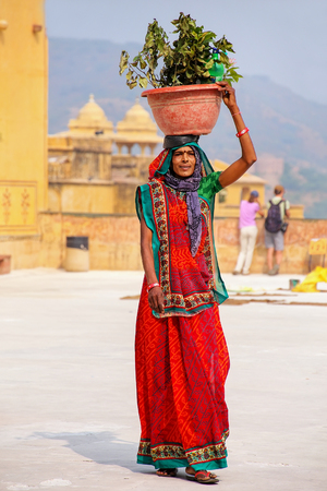 Local woman walking with a pot on her head in the second courtyard of Amber Fort, Rajasthan, India. Amber Fort is the main tourist attraction in the Jaipur area.