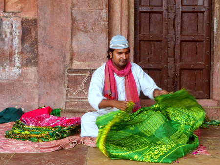Local man folding cloth inside Jama Masjid in Fatehpur Sikri, Uttar Pradesh, India. The mosque was built in 1648 by Emperor Shah Jahan and dedicated to his daughter  Jahanara Begum