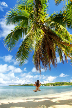 Young woman swinging on a rope swing (blurred motion) at the beach, Nananu-i-Ra island, Fiji. Tourism is the main industry of Nananu-I-Ra Stock Photo