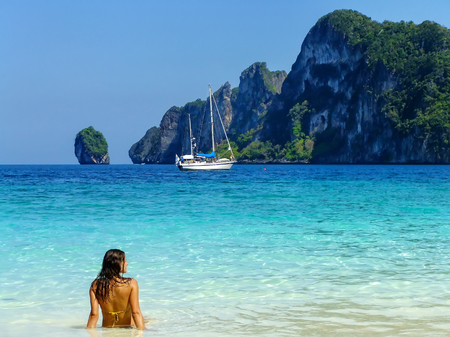 Young woman in bikini sitting at Ao Yongkasem beach on Phi Phi Don Island, Krabi Province, Thailand. Koh Phi Phi Don is part of a marine national park.