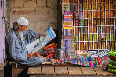 Local man reading newspaper at the street market in Fatehpur Sikri, Uttar Pradesh, India. The city was founded in 1569 by the Mughal Emperor Akbar, and served as the capital of the Mughal Empire from 1571 to 1585 Редакционное