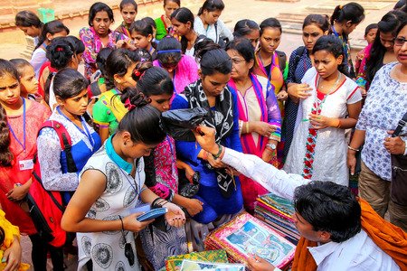 Group of girls buying cloth in the courtyard of Jama Masjid, Fatehpur Sikri, Uttar Pradesh, India. The mosque was built in 1648 by Emperor Shah Jahan and dedicated to his daughter  Jahanara Begum