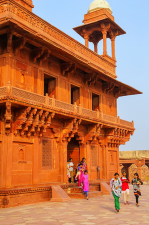 Young women walking out of Diwan-i-Khas (Hall of Private Audience)  in Fatehpur Sikri, Uttar Pradesh, India. Fatehpur Sikri is one of the best preserved examples of Mughal architecture in India.