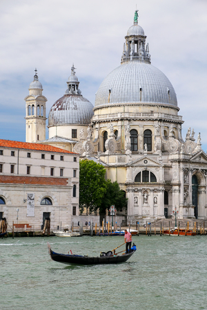 Gondola moving in front of Basilica di Santa Maria della Salute in Venice, Italy. This church was commisioned by Venice's plague survivors as thanks for salvation.