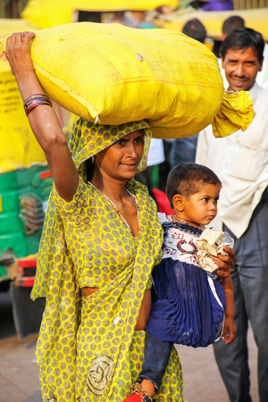 Local woman with little girl carrying bag on her head at Kinari Bazaar in Agra, Uttar Pradesh, India. Agra is one of the most populous cities in Uttar Pradesh
