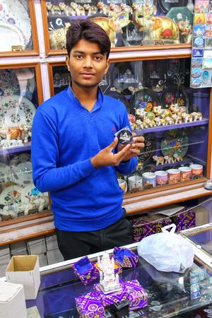 Young man working in a souvenir shop in Taj Ganj neighborhood of Agra, Uttar Pradesh, India. Agra is one of the most populous cities in Uttar Pradesh