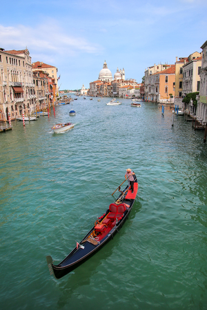 Gondola moving on Grand Canal in Venice, Italy. Venice is situated across a group of 117 small islands that are separated by canals and linked by bridges. Editorial