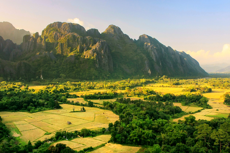 Aerial view of farm fields and rock formations in Vang Vieng, Laos. Vang Vieng is a popular destination for adventure tourism in a limestone karst landscape.