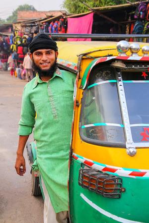 Young man driving tuk-tuk at Kinari Bazaar in Agra, Uttar Pradesh, India. Agra is one of the most populous cities in Uttar Pradesh
