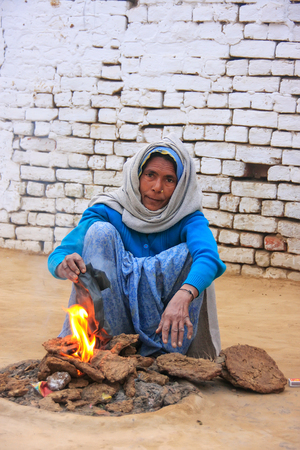 Local woman making fire using dry cow dung in Taj Ganj neighborhood of Agra, Uttar Pradesh, India. A disadvantage of using this kind of fuel is increased air pollution