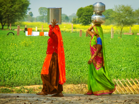 Local women carrying water jugs on their heads in the countryside near Agra, Uttar Pradesh, India. Drinking water supply and sanitation in India continue to be inadequate.