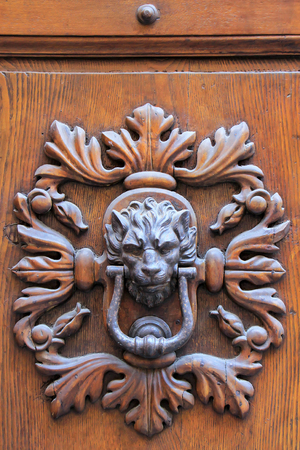 Door knocker in Montalcino town, Val d'Orcia, Tuscany, Italy. Towns of Tuscany are famous for door knockers with interesting designs.