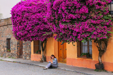 Young woman reading book on a sidewalk in historic quarter of Colonia del Sacramento, Uruguay. It is one of the oldest towns in Uruguay