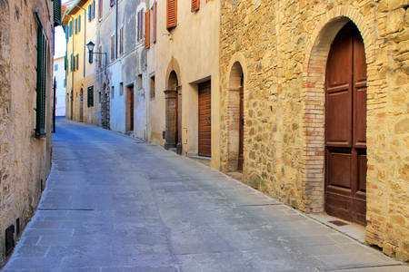 Narrow street in historic center of  Montalcino town, Val d'Orcia, Tuscany, Italy. The town takes its name from a variety of oak tree that once covered the terrain.