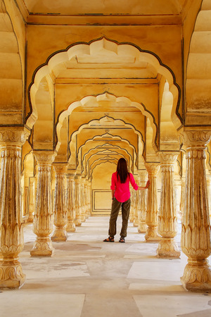 Young woman standing in Sattais Katcheri Hall, Amber Fort, Jaipur, India. Amber Fort is the main tourist attraction in the Jaipur area.