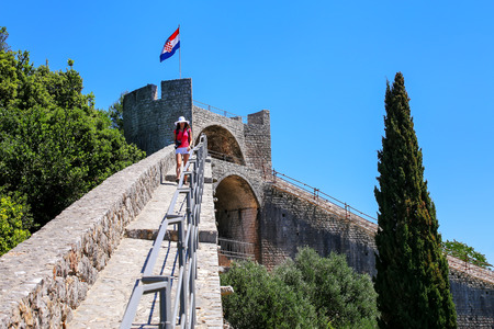Young woman walking on the defensive wall of Ston town, Peljesac Peninsula, Croatia. Ston was a major fort of the Ragusan Republic