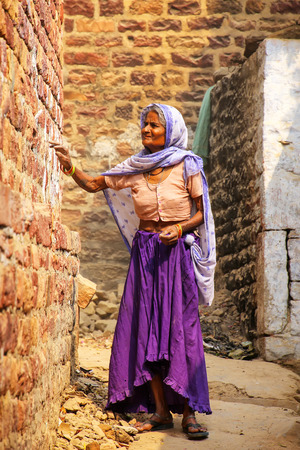 Local woman standing in a narrow street in Fatehpur Sikri, Uttar Pradesh, India. The city was founded in 1569 by the Mughal Emperor Akbar, and served as the capital of the Mughal Empire from 1571 to 1585 Banque d'images - 117737352