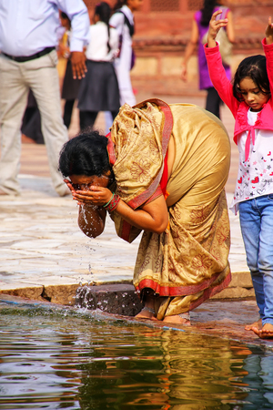 Woman washing in a pool in the courtyard of Jama Masjid in Fatehpur Sikri, Uttar Pradesh, India. The mosque was built in 1648 by Emperor Shah Jahan