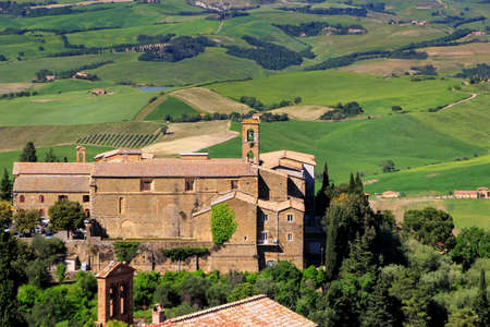 Old church and farm fields in Montalcino town, Val d'Orcia, Tuscany, Italy. The town takes its name from a variety of oak tree that once covered the terrain. 版權商用圖片