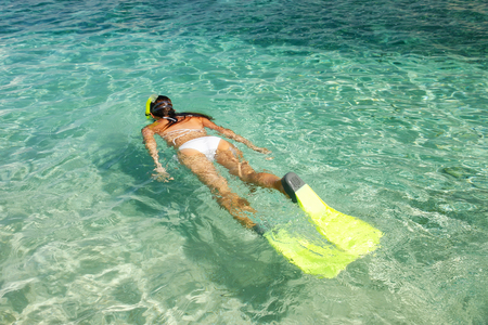 Young woman snorkeling in clear shallow water near tropical island