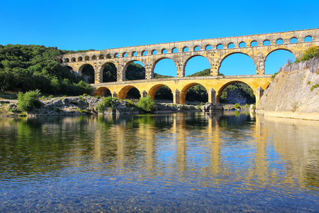 Aqueduct Pont du Gard reflected in Gardon River, southern France. It is the highest of all elevated Roman aqueducts.