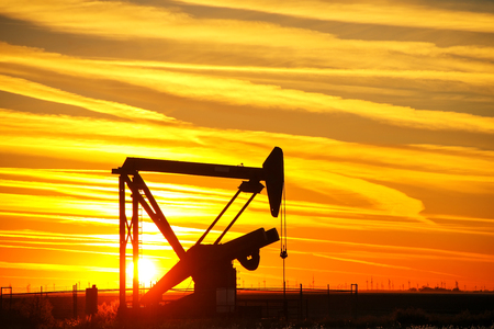 Silhouetted pump jack in the oil field at sunset Stock Photo