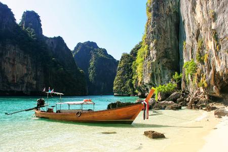 Longtail boat anchored by secluded beach on Phi Phi Leh Island, Krabi province, Thailand. Koh Phi Phi Leh is part of Mu Ko Phi Phi National Park.
