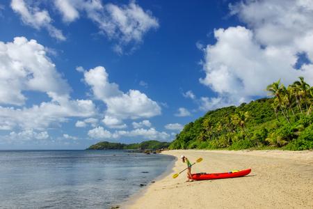 Young woman with red sea kayak on a sandy beach, Drawaqa Island, Yasawas, Fiji Imagens