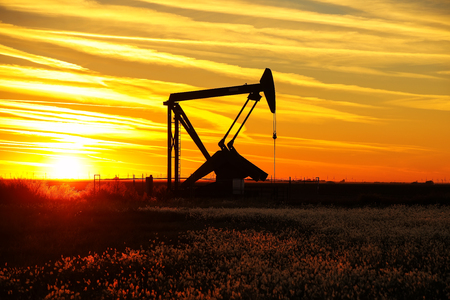 Silhouetted pump jack in the oil field at sunset Stok Fotoğraf