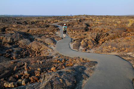Woman walking on a trail to the cave area, Craters of the Moon National Monument, Idaho, USA.