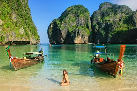 Young woman sitting on the beach at Maya Bay on Phi Phi Leh Island, Krabi Province, Thailand. Koh Phi Phi Leh is part of Mu Ko Phi Phi National Park.