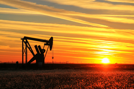 Silhouetted pumpjack in the oil field at sunset