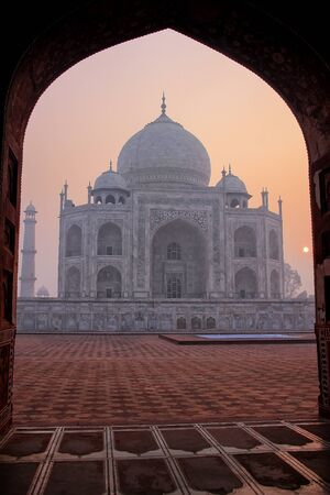 Taj Mahal at sunrise framed with the arch of the mosque, Agra, Uttar Pradesh, India. Stock Photo
