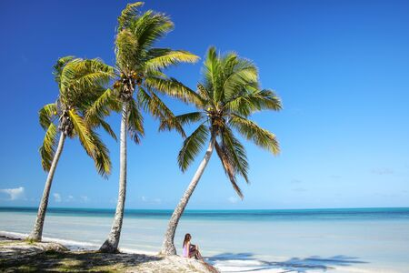 Woman sitting by the palm trees on the coast of Ouvea lagoon on Ouvea Island, Loyalty Islands, New Caledonia. Stok Fotoğraf