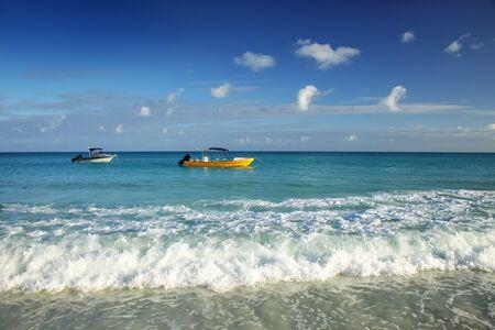 Boats anchored at Fayaoue beach on the coast of Ouvea lagoon, Mouli and Ouvea Islands, New Caledonia.
