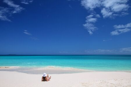 Woman relaxing on Fayaoue beach on the coast of Ouvea lagoon, Mouli and Ouvea Islands, New Caledonia.