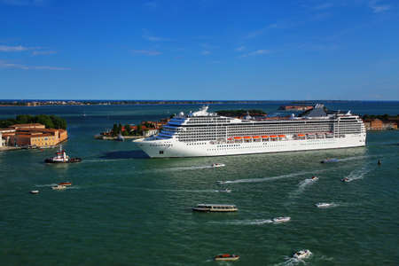 Cruise ship moving through San Marco canal in Venice, Italy. Venice is situated across a group of 117 small islands that are separated by canals and linked by bridges. Stock Photo