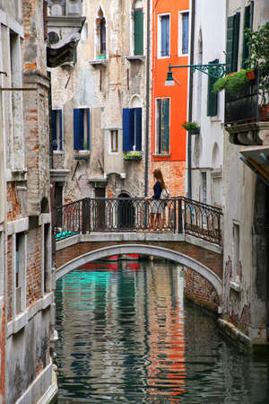 Houses along narrow canal connected by a stone bridge in Venice, Italy. Venice is situated across a group of 117 small islands that are separated by canals and linked by bridges. Stock Photo