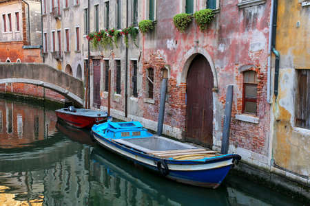 Boats moored in a narrow canal in Venice, Italy. Venice is situated across a group of 117 small islands that are separated by canals and linked by bridges.