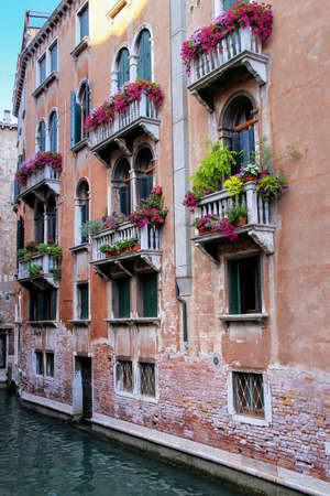 Building with flower boxes on the balconies in a narrow canal, Venice, Italy. Venice is situated across a group of 117 small islands that are separated by canals and linked by bridges.
