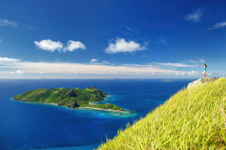 View of Kuata Island from Wayaseva Island with a hiker standing on a rock, Yasawa Islands, Fiji