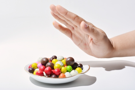 resist: Female hands gesture to rejecting color full chocholate Stock Photo