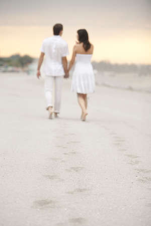 couple holding hands goes away leaving footprints on the sand