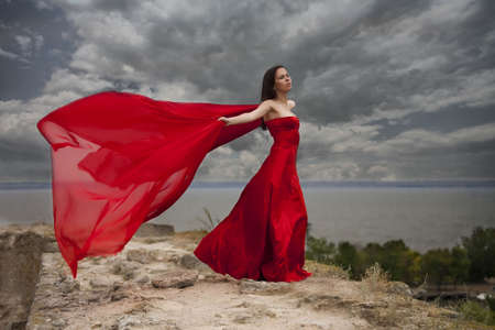 woman in red dress with red scarf before the storm