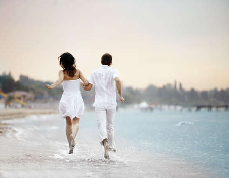 couple holding hands running away over the beach