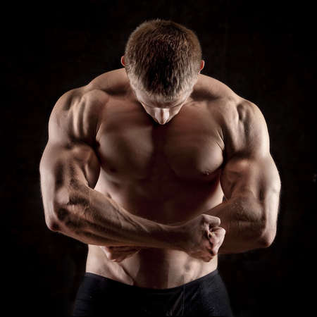 male bodybuilder: strong athletic man on black background