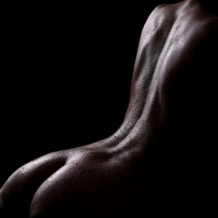 anatomy naked woman: artistic nude studio shoot of woman body parts with water drops on black background