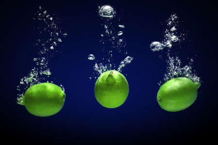 Fresh lime dropped into water with bubbles photo